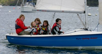 An instructor and 4 children sailing a dinghy having fun at mylor sailing school falmouth