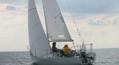 Three adults sailing on a J24 keelboat at Mylor Sailing School near Falmouth, Cornwall