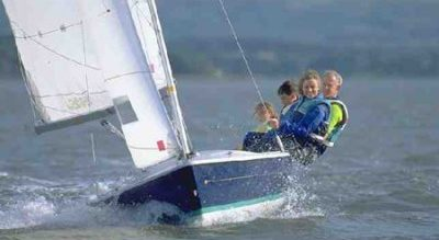 group of 4 people on a blue sailing dinghy learning to sail with Mylor Sailing School