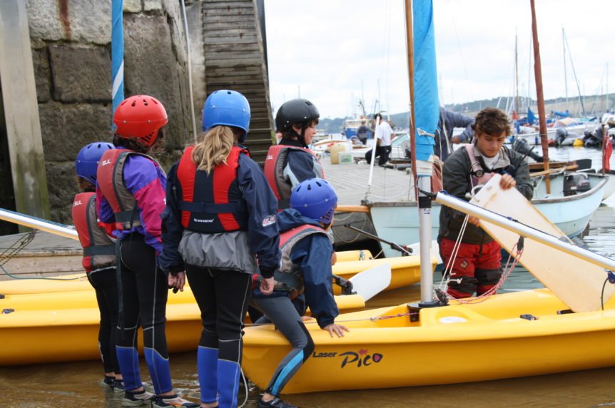 Group of children launching their boats at a slipway at Mylor Sailing School in Cornwall