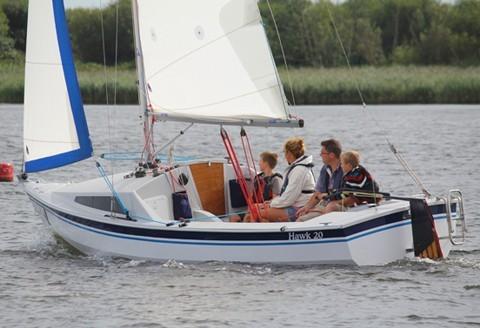 Family sailing on an accessible sailing boat at Mylor Sailing School near Falmouth, Cornwall