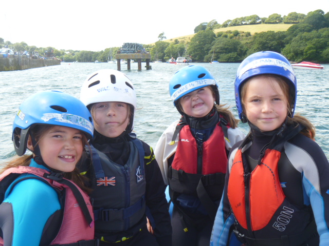 Four children with helmets on ready for sailing at Mylor Sailing School in Cornwall