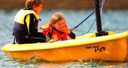 Two children sailing in a small yellow boat in Cornwall