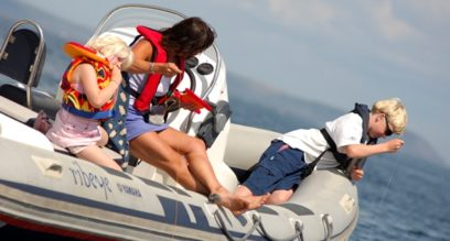 Mother and two young children crabbing from a small motorboat on a sunny day at Mylor Sailing School near Falmouth, Cornwall