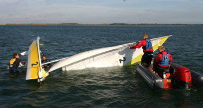 Two young adults rescuing a sailing dinghy from a capsize with two sailors in the water at Mylor Sailing School near Falmouth, Cornwall