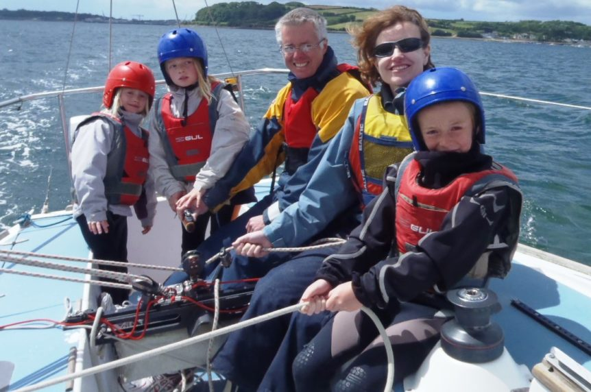 Family of five learning to sail on a keelboat in Mylor Cornwall