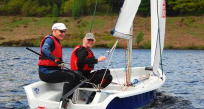 Two men sailing a Laser 2000 dinghy having fun at Mylor Sailing School Falmouth in Cornwall