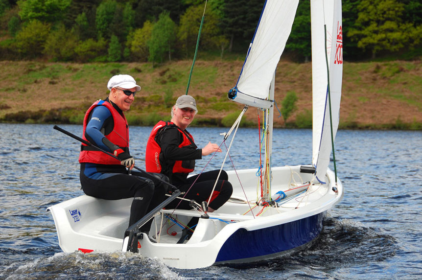 Two men sailing a Laser 2000 dinghy having fun at Mylor Sailing School Falmouth in Cornwall