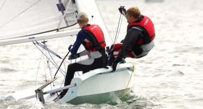 Two teenagers sailing a dinghy and trapezing at Mylor Sailing School in Falmouth Cornwall