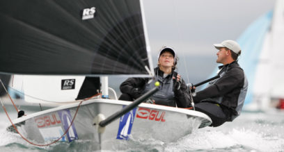 Two people sailing with a black spinnaker on a performance dinghy