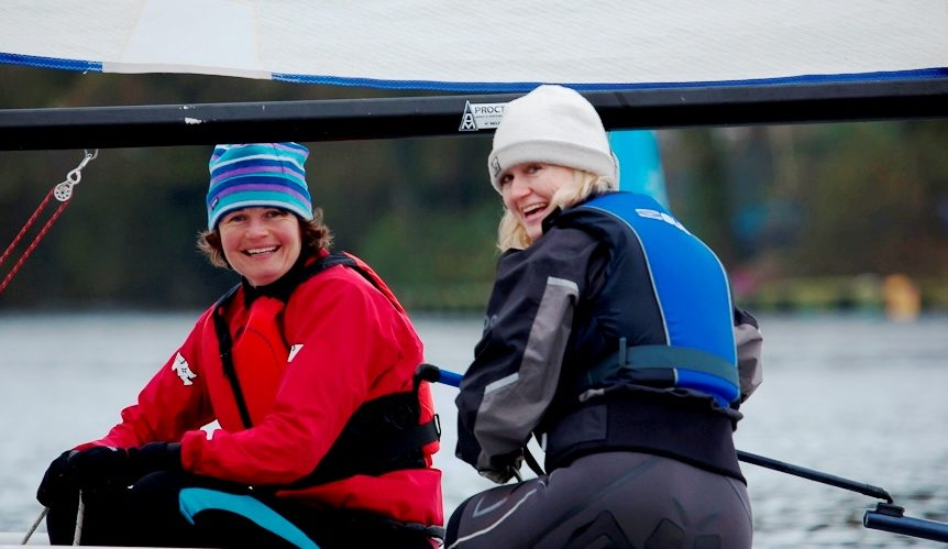 Two ladies smiling sailing a small dinghy at Mylor Sailing School near Falmouth Cornwall