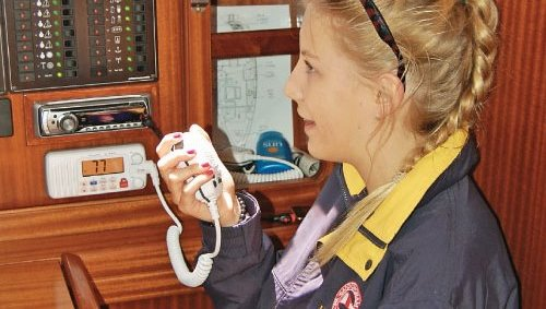 lady operating a fixed VHF radio down below deck on a yacht at mylor sailing school near Falmouth, Cornwall