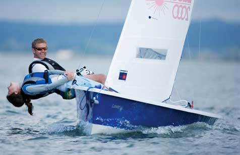 Two people hiking out a lot in a Laser 2000 sailing dinghy at Mylor Sailing School in Falmouth, Cornwall