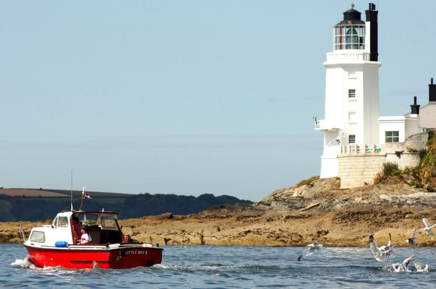 Small red boat motoring past St Anthony's light house at Mylor Sailng School near Falmouth, Cornwall