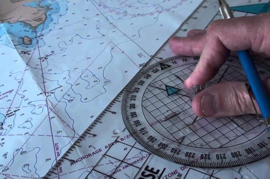 Portland plotter on a chart with someone's hand at Mylor Sailing School Cornwall