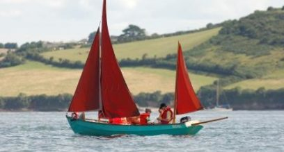 family sailing in a blue boat with red sail at mylor sailing school near Falmouth