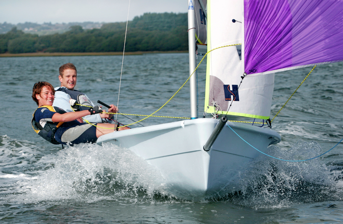 A man and a lady sailing fast with a purple spinnaker sail at mylor Sailing School in falmouth, Cornwall