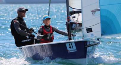 Two adults sailing a Laser 2000 dinghy with blue spinnaker sail at Mylor Sailing School near Falmouth, Cornwall