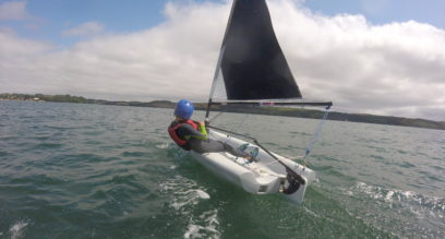 Young boy sailing a small dinghy with helmet on a sunny day at Mylor Sailing School near Falmouth, Cornwall