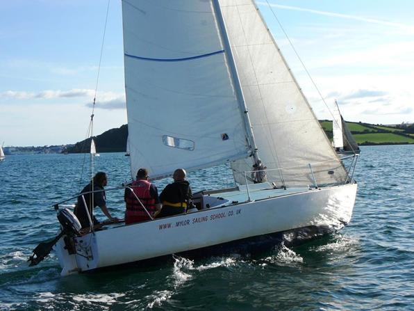 Three adults sailing on a 24 foot keelboat at Mylor Sailing School