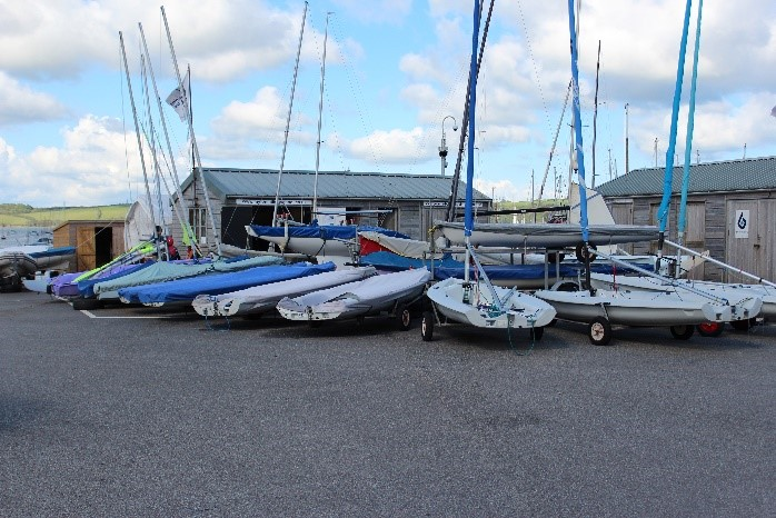Large level area with sailing dinghies parked outside wooden huts at Mylor Sailing School