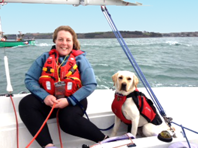 Lady sailing a dinghy with assistance dog at Mylor Sailing School Falmouth Cornwall