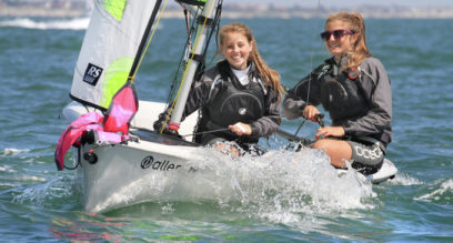 Two teenage girls having fun sailing a RS Feva dinghy on a sunny day at Mylor Sailing School near Falmouth, Cornwall