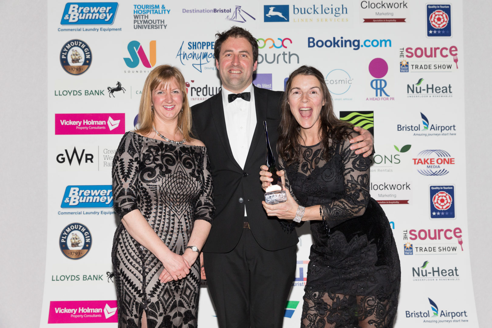 Three people in black tie holding a tourism award for Mylor Sailing School near Falmouth