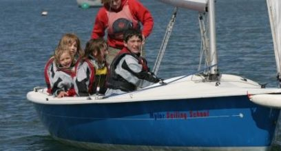Female instructor and group of four children sailing together in a blue dinghy at Mylor Sailing School Falmouth Cornwall