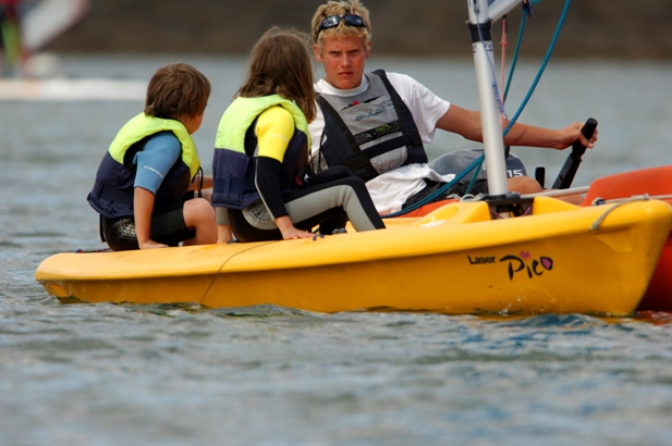 Sailing instructor teaching 2 children in a dinghy at Mylor Sailing School Falmouth Cornwall