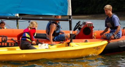 2 instructors teaching a child to sail from a rescue boat at Mylor Sailing School in Falmouth Cornwall