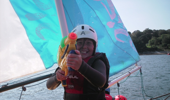 young girl with water pistol on a sailing dinghy having fun at Mylor Sailing School Falmouth Cornwall