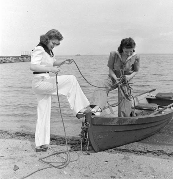 Two ladies in a black and white photo holding a rope on a small rowing boat at Mylor Sailing School Falmouth Cornwall