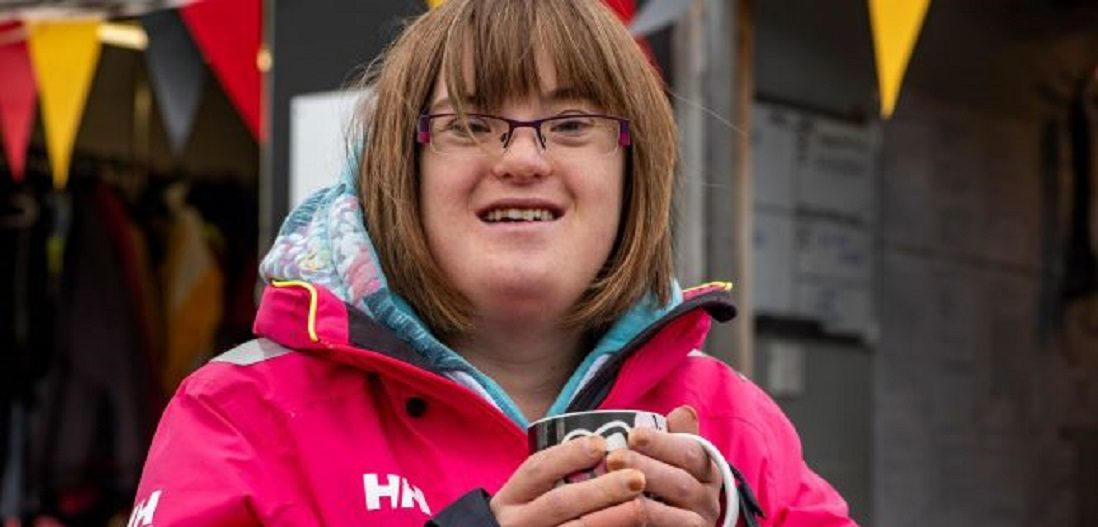Girl with Downs Syndrome smiling and drinking a cup of tea at Mylor Sailing School Falmouth Cornwall