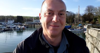 Man stood by the water smiling Simon Chapman a trainer at Mylor Sailing and Powerboat School Falmouth Cornwall