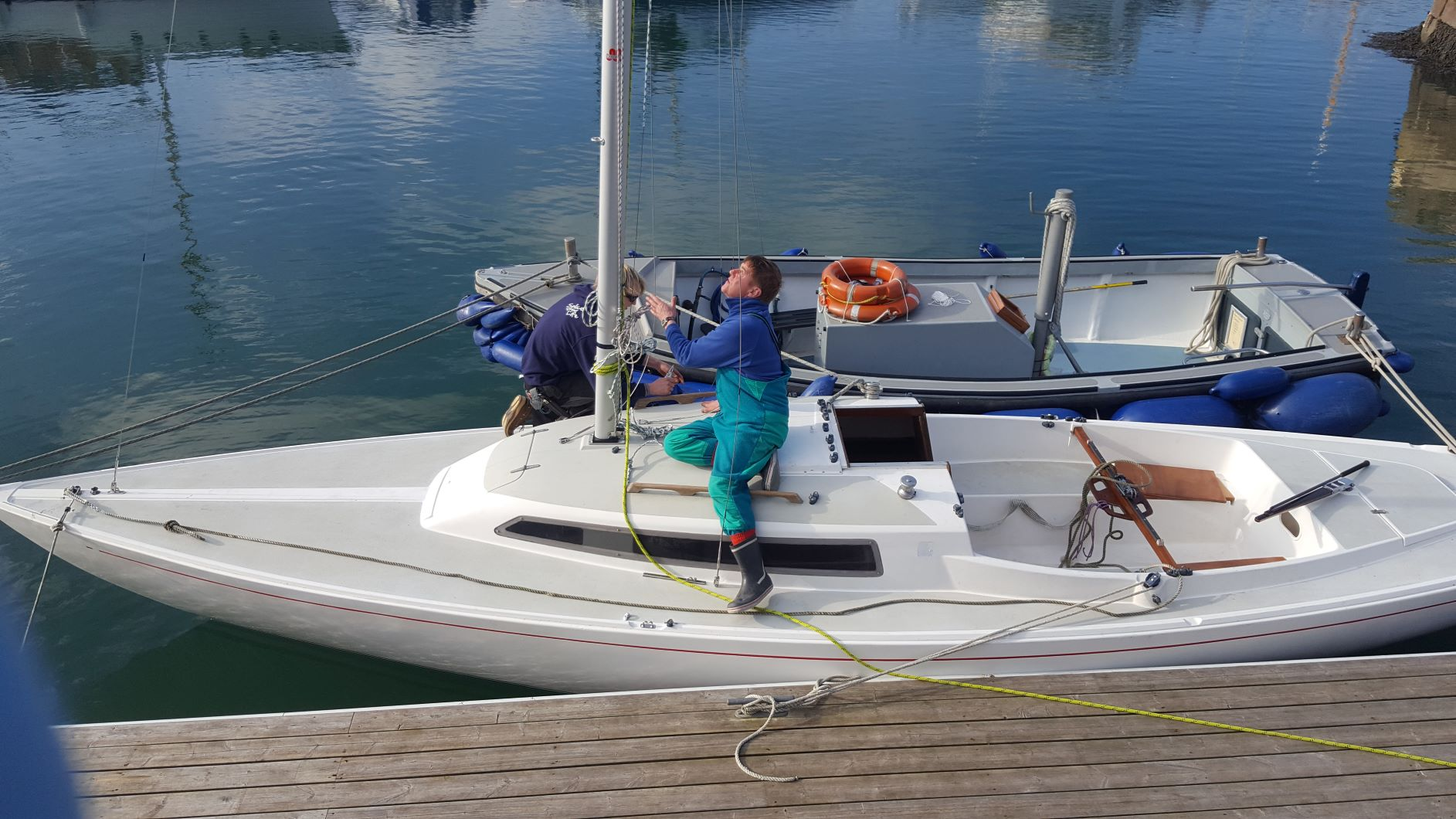 person helping to rig the mast on H Boat alongside pontoon at Mylor Sailing School Falmouth Cornwall