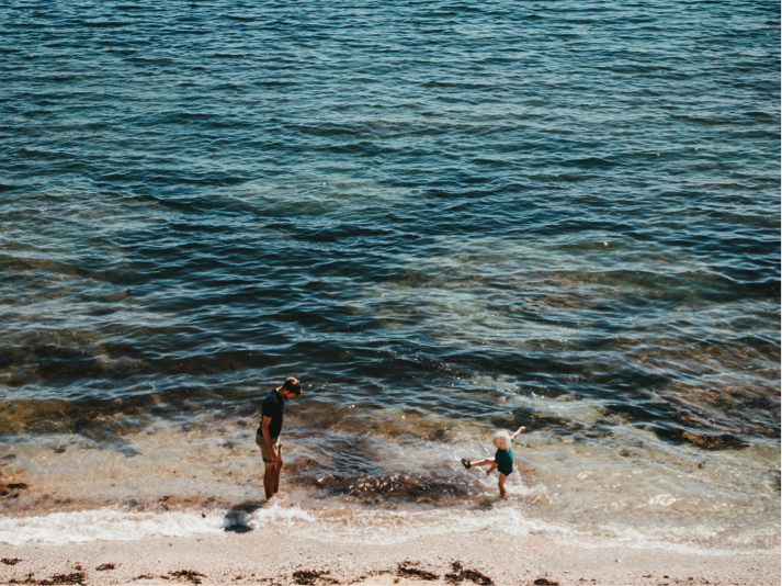 gylly beach, with a man and child playing in the shallows