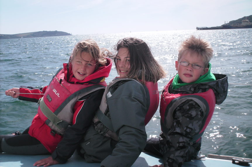 Three children sailing on a keelboat in sunny Falmouth at Mylor Sailing and Powerboat School Falmouth Cornwall