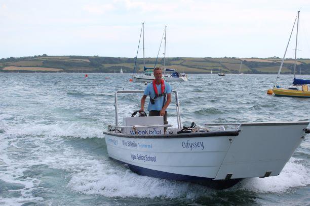man driving accessible powerboat at Mylor Sailability Falmouth Cornwall